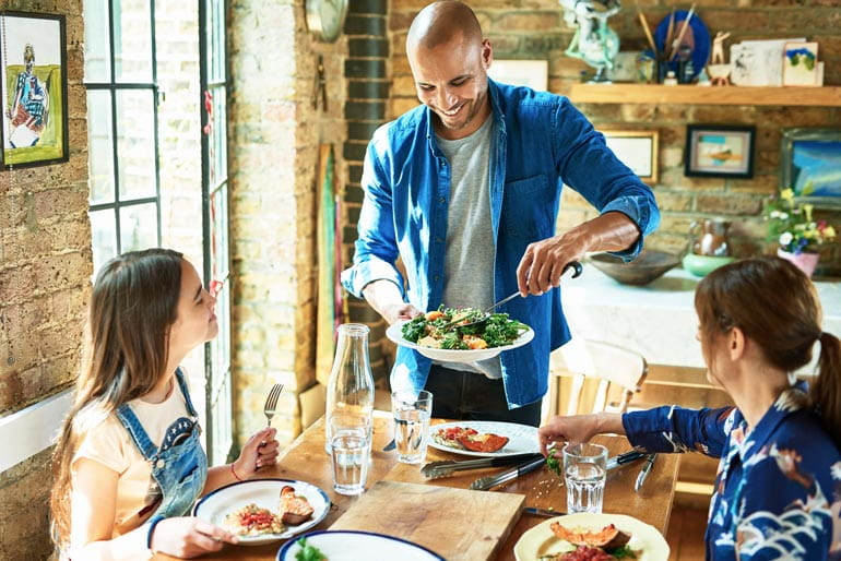 Father serving healthy dinner to family