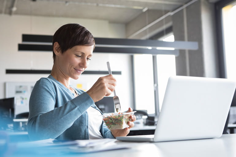 Woman at office eating healthy lunch during break